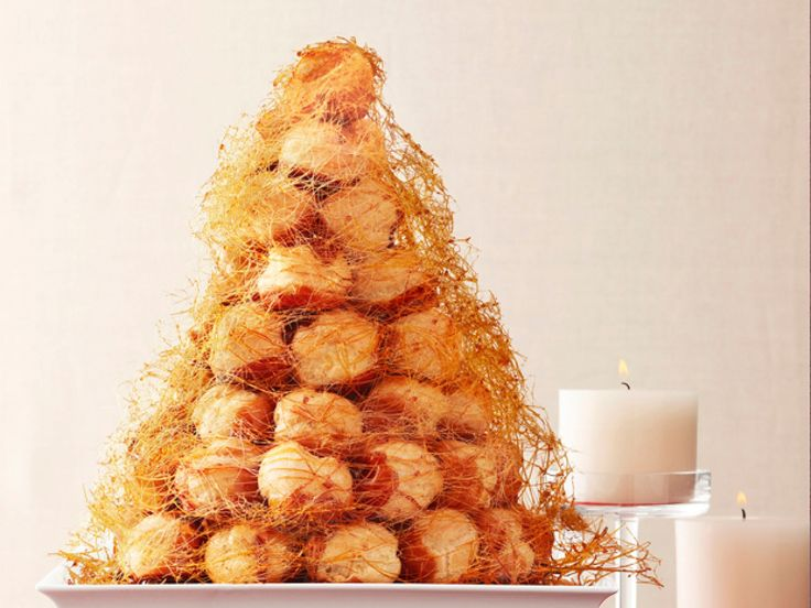 """Croquembouche : Croquembouche (pronounced kroh-kuhm-BOOSH) is French for """"crisp in mouth."""" The crunch comes from the caramel coating on each puff."""