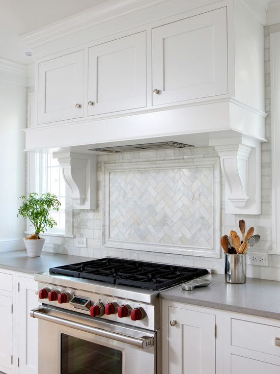 Caesarstone Pebble; Love herringbone/chevron tile within the picture frame molding over the stove