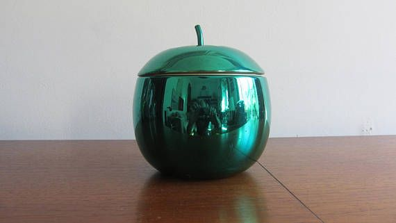 Iconic vintage, very bright and shiny, metal green ice bucket, in the shape of an apple, with a green metal stem/handle on the top, made in the 1960s. This original cult object is made of light weight metal/anodized aluminum. It has an insulating white plastic inside, that can be removed for cleaning, and its complete with a very nice handle on the top, made of a green metal stem. This lovely ice bucket is not marked. A fun addition to any Mid Century Modern or contemporary interior...