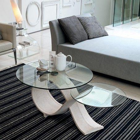 ALPHA. Il tavolino Alpha si distingue per eleganza e dinamismo. La sua base in agglomerato è formata da un nastro che si incrocia e crea due basi d'appoggio per i piani in vetro trasparente.