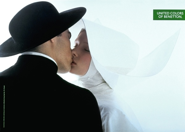 """A priest kissing a nun was one of many advertisements that depicted religious and sexual conflict for Benetton. The fall 1991 ad campaign of a not-so-platonic kiss between a priest and a nun clad in an old-fashioned habit immediately sparked controversy across the world. Benetton stated that the ad was merely """"the affirmation of pure human sentiment"""". Year: 1991 Photographer: Olivero Toscani"""