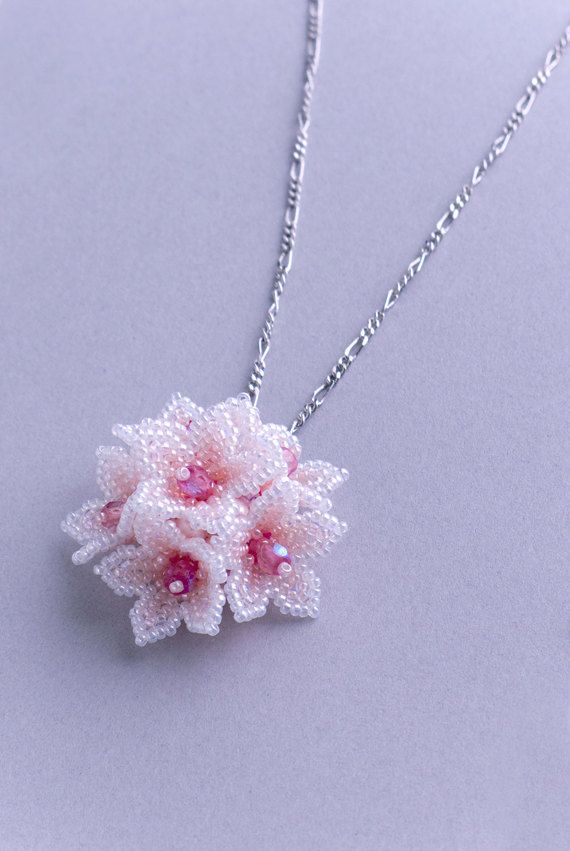 This cute flower pendant is composed of 6 pieces of flowers. A flower is star-shaped and woven with 1.5mm seed beads. The pendant is domed and the back is flat and patterned. This pink & white was inspired by the color of cherry blossoms.  Dimensions: Chain Necklace: 45cm (length) x 2mm (width) Pendant : 3.5cm (height) x 3.5cm (width) x 1.8cm (thick)  * If you wish to change the length of a chain necklace, please let me know the length you desire. * You can also purchase only pendant. * You…