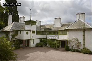 Perrycroft, Colwall, Herefordshire, . II*  House. Begun 1893 and dated 1895 by C F A Voysey for J Wilson, MP, a railway magnate, in 'eclectic' Arts and Crafts and incipient Art Nouveau styles. Roughcast, grey slate 45 degree hipped roof with tapered finials to 2 hip junctions, deep eaves supported by slender iron brackets, 5 stacks 3 of which are battered and one punctured by an arch. 'U' plan, service wing in longer north-east arm, the bottom of the 'U' is the garden fro