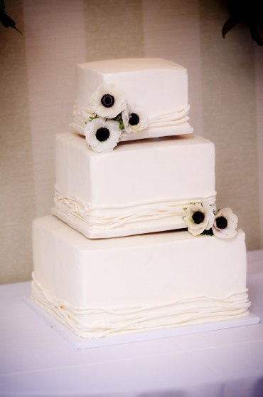 Simple square tiered wedding cake adorned with anemone flowers