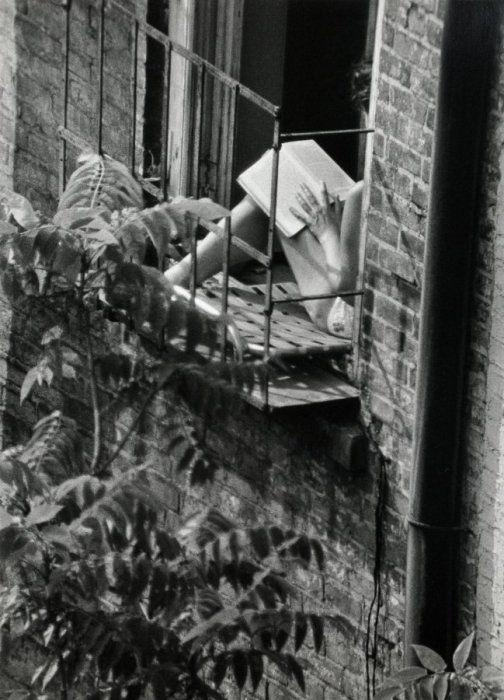 Woman reading in fire escape window, Greenwich Village, New York, 1963 • Photograph by André Kertész