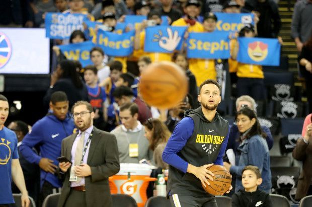 Fans hold sings as Golden State Warriors' Stephen Curry (30) warms up before the start of the game against the Oklahoma City Thunder at Oracle Arena in Oakland, Calif., on Tuesday, Feb. 6, 2018. (Ray Chavez/Bay Area News Group)