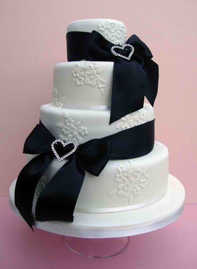A gorgeous vintage wedding cake wrapped with black ribbons.