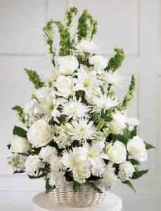 A Round Willow Basket Holds Pure White Flowers As A Symbol Of Light All White Roses With Images White Flower Arrangements Church Flower Arrangements Funeral Arrangements
