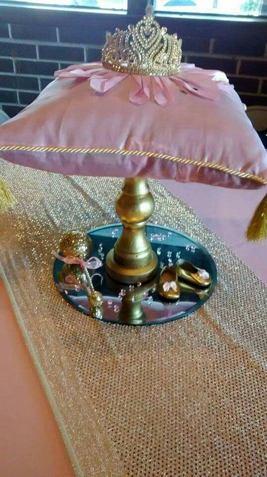 Pink and gold little princess baby shower...DIY pillow with tiara, glitter rattle and baby shoes centerpiece by Themes Do Come True