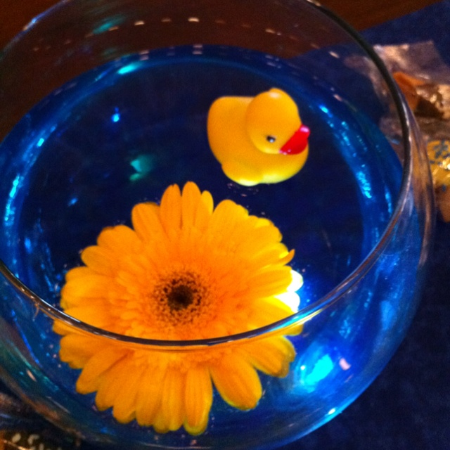 Centerpieces I made for my girlfriends rubber duck baby shower <3 floating duck, gerber daisy and lights on the bottom of the fishbowl :-) super crafty and cute!