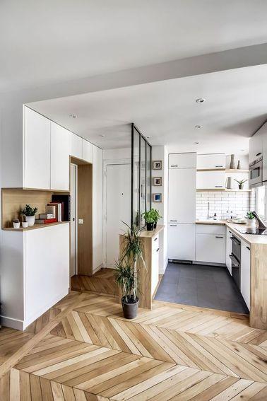 Ce petit appartement dans le huitième arrondissement à Paris a été bien pensé. La cuisine en U s'ouvre sur le séjour pour gagner le maximum de place, tout en créant une vraie entrée grâce à la verrière d'intérieur. Le carrelage métro et le mobilier épuré de cette petite cuisine blanche lui donnent un côté rétro que l'on retrouve dans le parquet massif en chevron du reste de l'appartement.