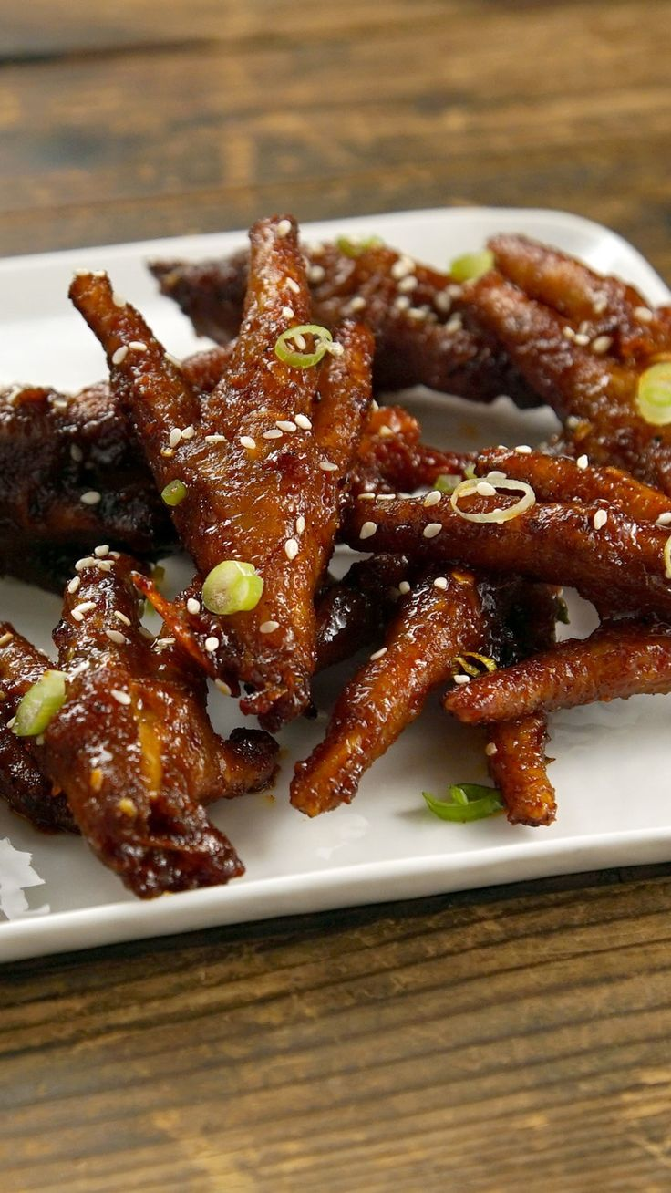 Recipe with video instructions: Who knew this crunchy Korean bar food was also great for your skin? Ingredients: 1 lb chicken feet, 2 Tbsp kosher salt, ¼ cup soju, For the sauce:, 1 Tbsp gochujang, 2 Tbsp cheongyang gochugaru (extra-spicy gochugaru) or regular gochugaru, 1 Tbsp sugar, 1 Tbsp soy sauce, 1 Tbsp oyster sauce, 1 Tbsp mirin, 3 garlic cloves, chopped, ½ tsp grated ginger, 3 Thai chili, chopped, ¼ tsp black pepper, To garnish:, Green onion, Sesame seeds, Sesame oil