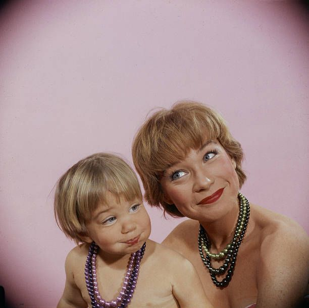 Portrait of American actress Shirley Maclaine and her two 1/2 year old daughter Sachi Parker as they make faces during a photo shoot January 1959