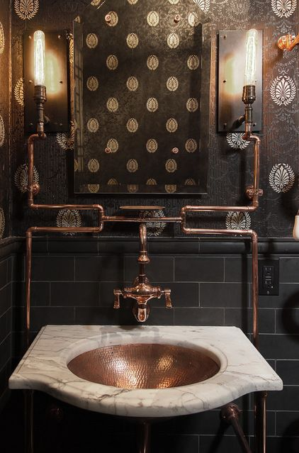 Exposed copper piping against black tile and wallpaper creates a beautiful focal point in this steampunk-inspired powder room. Also used for the fixtures and sink, copper is a great warming element in the room.