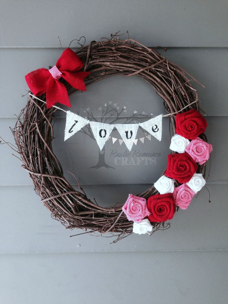 """Show your love with this sweet wreath! This 18"""" grapevine wreath is embellished with red, pink and white burlap flowers and a """"love"""" mini banner. **This item is handcrafted to order. Please allow 2-3 days for production**"""