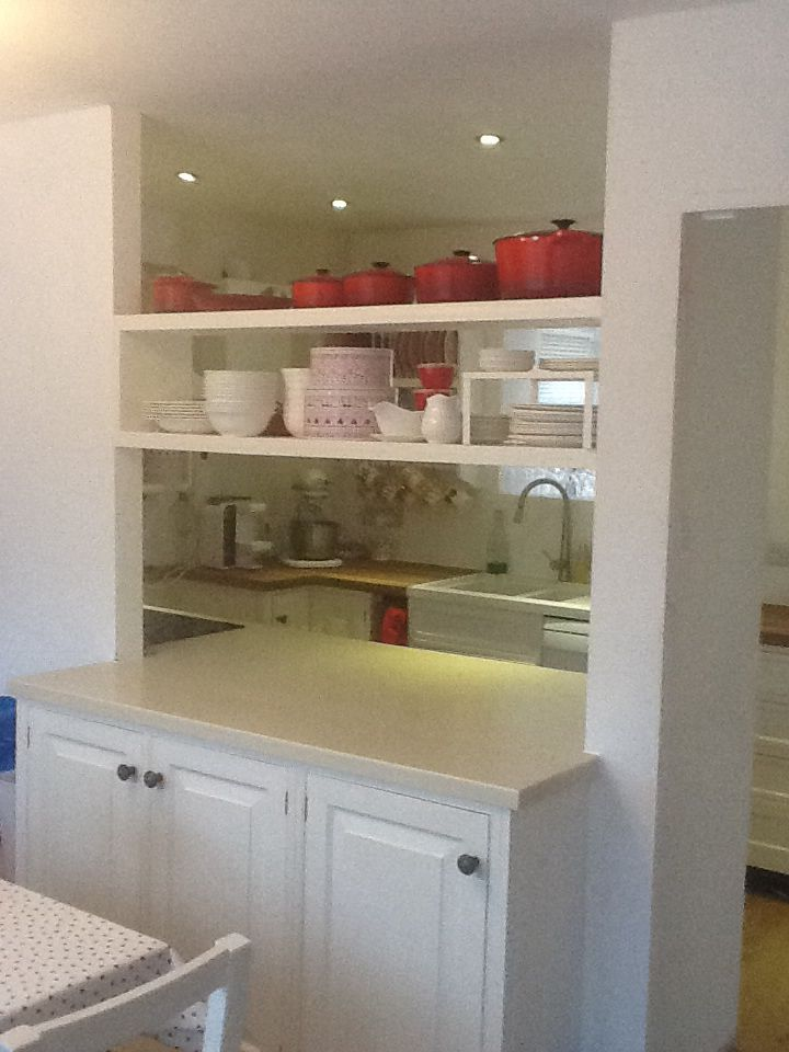 Kitchen through dining room serving hatch/ island style unit with cupboards both sides.