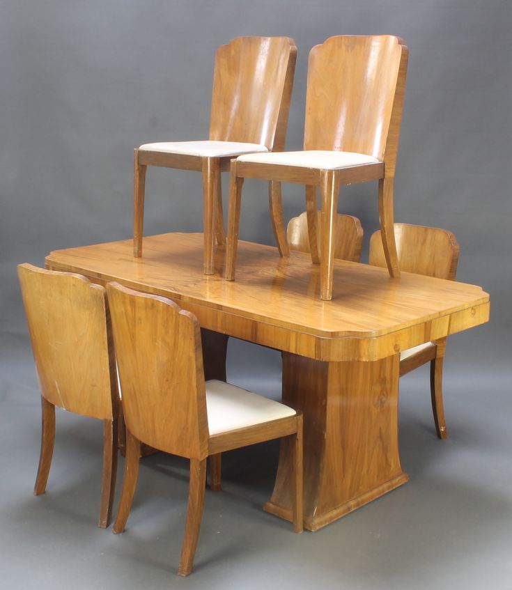 """Lot 1012, Epstein, an Art Deco walnut dining suite comprising rectangular dining table with quarter veneered top 31""""h x 66""""l x 35""""w together with a set of 6 tub back dining chairs with drop in seats, matching cocktail cabinet with hinged lid fitted 1 long drawer above a cupboard flanked by 2 short drawers and double cupboard 49""""h x 54""""w x 17""""d complete with an H & L Epstein receipt dated 28-12-1953 for 455 pounds est £300-500"""