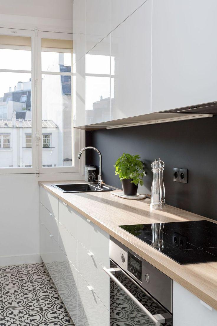 Une cuisine lookée avec meubles laqués, crédence noire et sol en carreaux de ciment