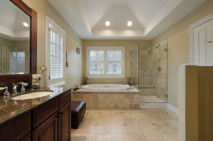 Master bathroom in luxury home with cathedral ceiling, tub, glass shower and dark vanity.  Simple, clean and I love the sitting area under the window.