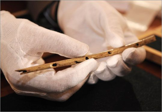 MUSIC. Professor Nicholas Conard of the University in Tuebingen shows a flute during a press conference in Tuebingen, southern Germany, on Wednesday.The thin bird-bone flute carved some 35,000 years ago and unearthed in a German cave is the oldest handcrafted musical instrument yet discovered.  The Boston Globe -