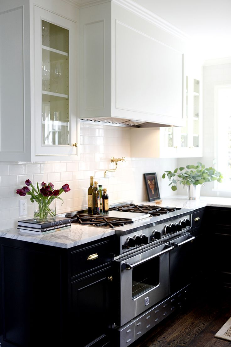 White kitchen cabinets with black marble countertops - Classic Kitchen With White Upper Cabinets And Black Lower Cabinets Marble Countertops And A White Subway Tile Backsplash