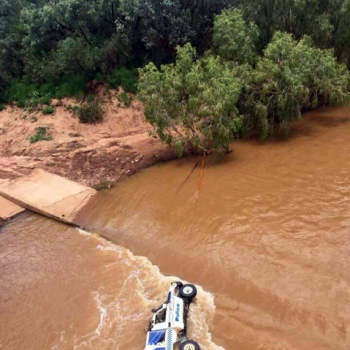 Two Northern Territory Police officers trek 14.5 kilometres to get help after their vehicle washes off a crossing near Katherine.