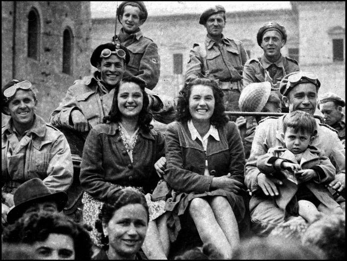 Bologna, 25 aprile 2013. Due giovani donne e un bambino in posa con dei soldati polacchi su un carro armato, dopo la liberazione della città da parte dalle truppe alleate.