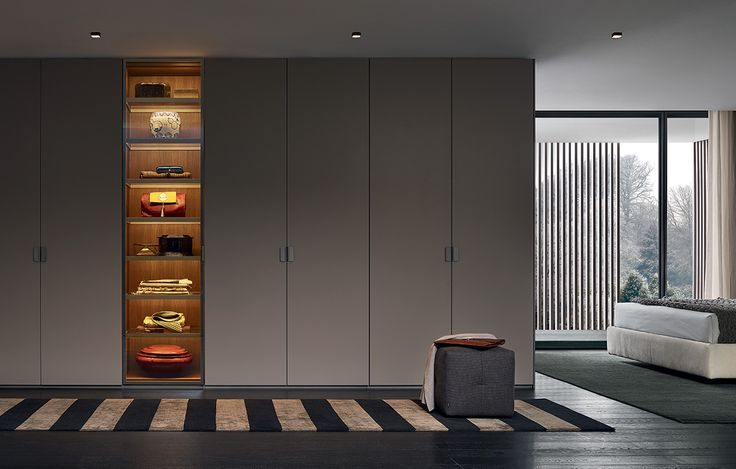 Senzafine Fitted wardrobes, leaf opening, arena mat lacquered and reflecting transparent glass doors, piombo painted Volo handles. Onda pouf in removable 04 lava Merida fabric.