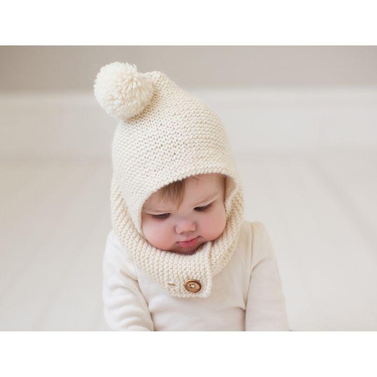 Cagoule style capuche pour bébé coloris écru avec pompon. Parfaitement ajustable à la tête de l'enfant grâce aux 2 rangées de boutonnières qui permettent de choisir la position des boutons.Tricoté au point mousse en France avec une laine douce, souple et naturelle : 60% alpaga, 40% laine.