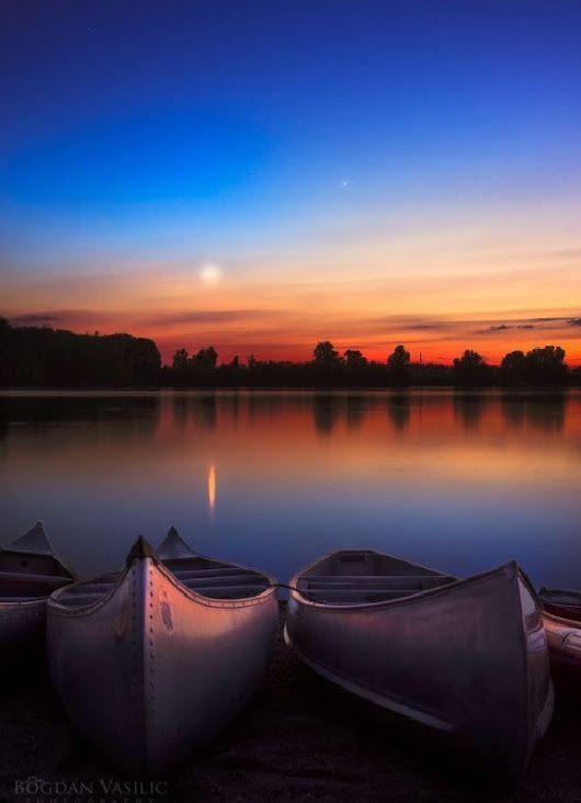 Sunset over canoes on a dusky lake