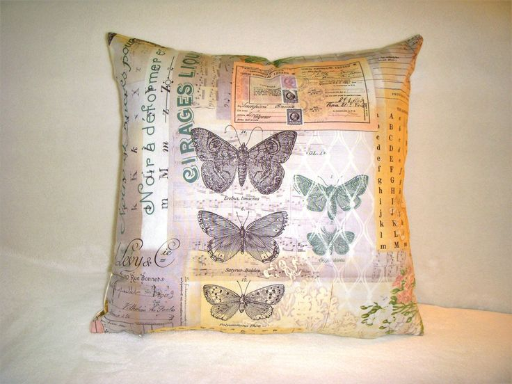 "Butterflies Pillow Cover Botanical Fabric Butterfly Nature Black Letters Script Stamps Numbers Green. This pillow cover is made from The Tim Holtz Electic Elements Wall Flower line of fabric. Measures 16"" square. The pattern is called Botanical. The beautiful center motif consists of black and green butterflies. The surrounding design consists of black letters, flowers, stamps, script and numbers. All in shades of green, lavender, peach, cream, pink and white. The back is made of a cream..."