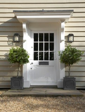 While I prefer a red door, I do like the plantings. White front door with pot plants  clapperboard Hampshire farmhouse  England  UK