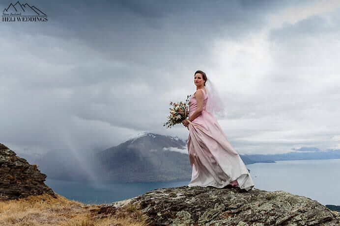 Bride in pink wedding dress on mountain top in Queenstown with stormy weather coming in