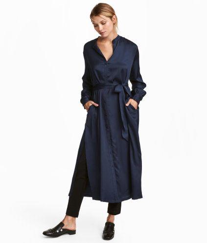 Mörkblå. En vadlång, rakt skuren klänning i vävd kvalitet med lätt lyster. Klänningen har låg ståkrage och knäppning fram. Avtagbart knytskärp i midjan och