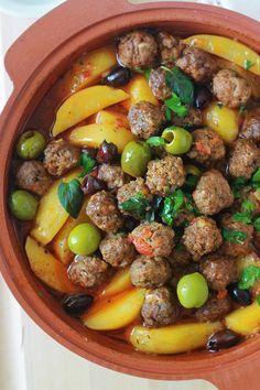Tajine aux boulettes de viande, pommes de terre et olives. Le tout est cuit dans une sauce tomate.Si vous n'avez pas de tajine en terre cuite, pas de problème. Utilisez une cocotte ou une grande poêle avec couvercle. Un plat simple, complet et réconfortant.