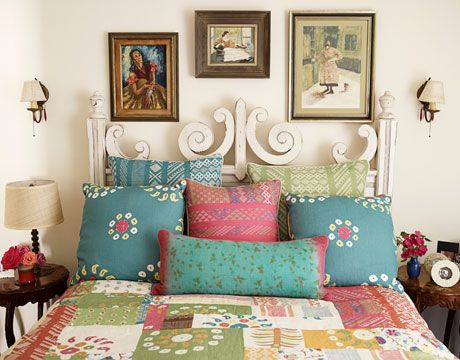 """""""I just can't live without color,"""" says Ireland, who made pillows and a patchwork quilt with fabrics from her new collection, including Tangier and Marrakech, for the guest bedroom. The bed, from Plantation, has a slightly distressed finish so it would look as if it had been shoved through a few doorways. The three paintings were originally scattered around the room; Ireland grouped them above the bed for more impact. Bedside lamp from Kathryn Ireland. Sconces from Liz's Antique Hardware."""
