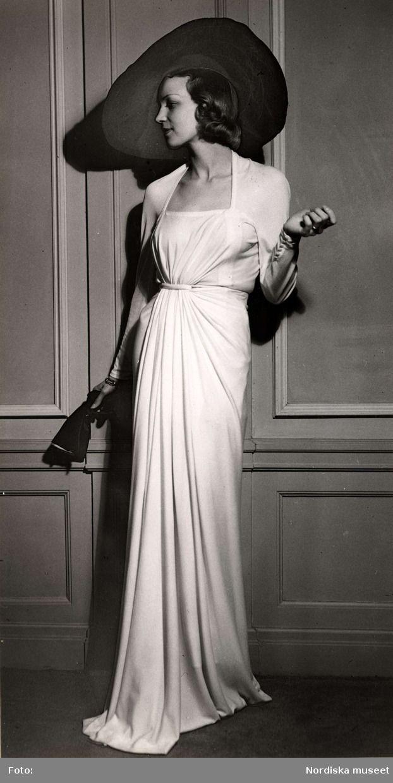 Produsent:Dammode, kvinnlig modell poserar iklädd draperad aftonklänning och vidbrättad hatt. I handen håller hon ett par handskar. Nordiska Kompaniet 1938. ID:Photograph Belongs to:NMA.0032098 Type:Nordiska museet