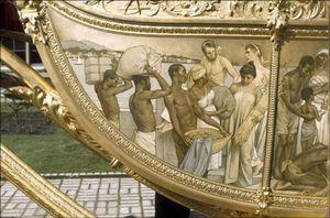 Hulde der Koloniën - Op het zijpaneel van de Gouden Koets worden halfnaakte zwarte mannen en vrouwen afgebeeld die hun rijkdommen aanbieden aan het koningshuis. Klik foto voor meer info.