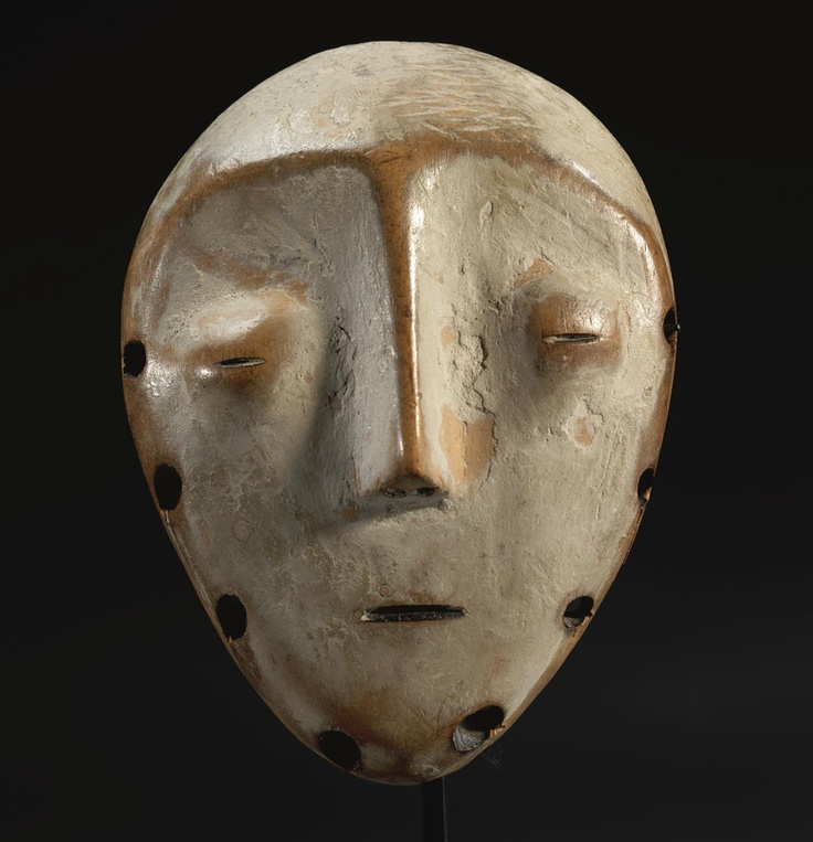 A FINE LEGA MASK, DEMOCRATIC REPUBLIC OF THE CONGO    of flat oval form, the human face with heart shaped facial plane, small mouth, long slender nose bisecting delicately bulbous coffee bean eyes and leading to high arched eybrows; '1787' on label on reverse; fine aged honey brown patina with kaolin on the front.  height 5 in. 12.7 cm