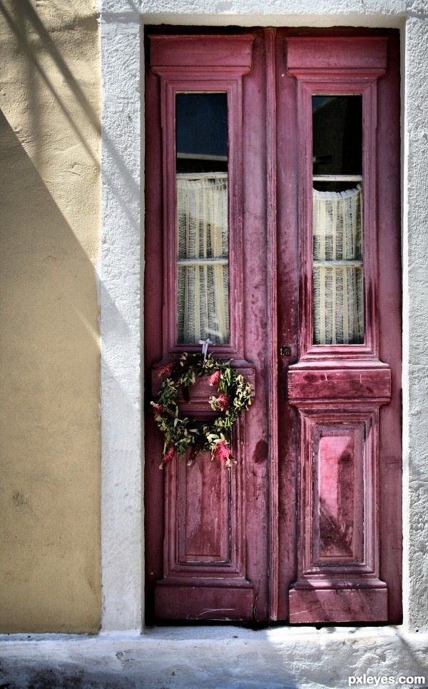 Old, weathered raspberry red/maroon/dark pink colored double doors with a wreath in Kefalonia, Greece.