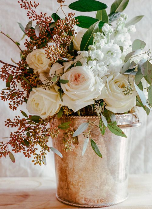Copper bucket with roses and beautiful white stock flowers and various berries other greenery. Lovely bouquet.