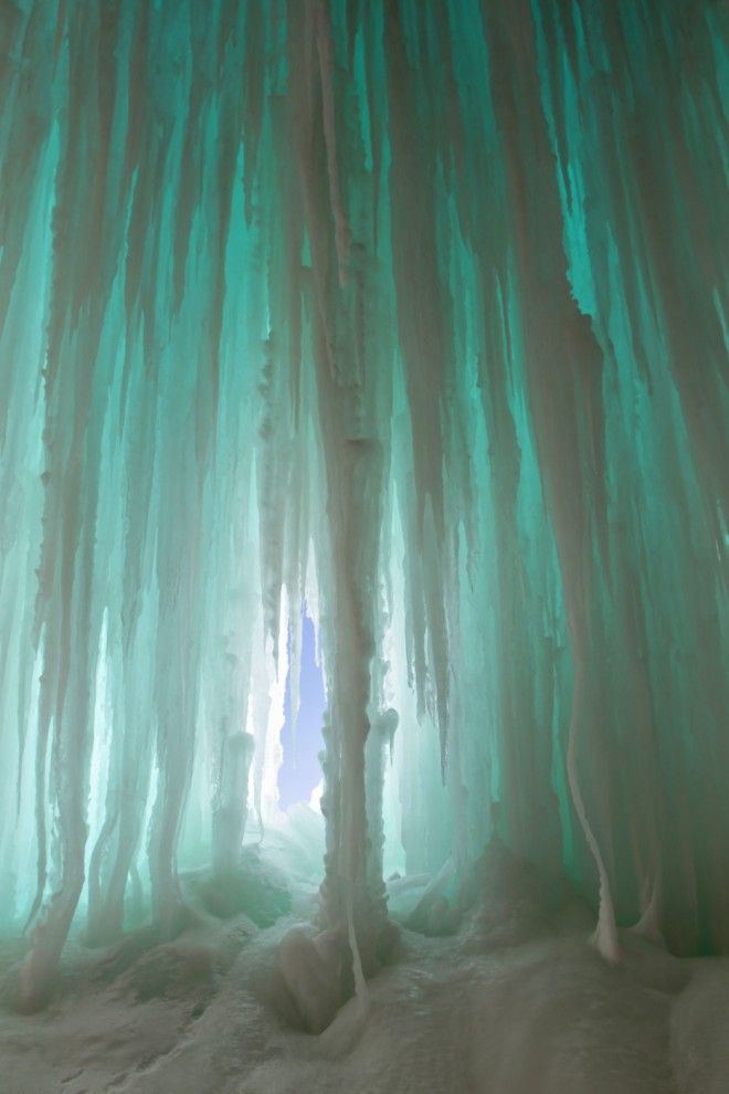 Lake Superior Ice Caves on Grand Island, just off the shore in Munising, Michigan. A short walk from Sand Point Beach across frozen Lake Superior will leave you at the base of ice curtains more than 30 feet tall and stretching hundreds of feet wide.
