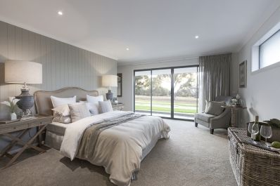 This French Provincial style master bedroom features rustic oak bedside tables and cabinets, layered grey decor and large classic table lamps. This is country living at its best. As featured in Charlton 33 at Eucalypt Estate.