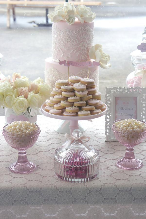Mesa de postres con torta decorada con un diseño de encaje.