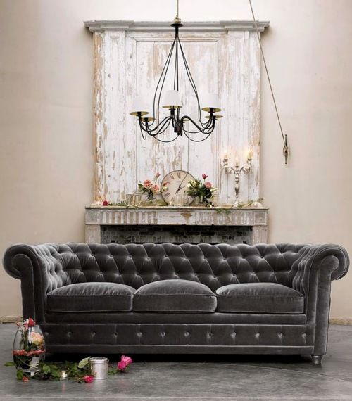 Wonderfully weathered, peeling paint covered fireplace and a tufted smoke grey sofa   I love this sofa!   Its gorgeous