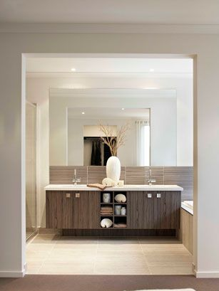 The cabinet doors are in Seductive Limba laminate by Laminex, with benchtops in Caesarstone Snow. The mottled Urbis floor tiles in Taupe and Airstrip mosaic glass tiles in Coco, both from Beaumont Tiles, echo the colour of the carpet in the adjoining room.