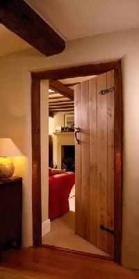Solid wood slat door with black hardware.
