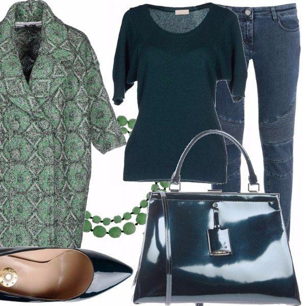 Jeans in denim blu con taglio modello motociclista, maglioncino con scollo tondo e maniche ampie, décolleté lucide verde petrolio, borsa in pelle lucida verde petrolio, collana con pietre color verde, soprabito con maniche a 3/4 in tessuto con fantasia geometrica retrò