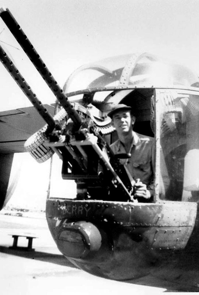 In the South Pacific in World War II, tail gunner Sgt. James E. Berryhill sits with a field modification of two .50-caliber M2 machine guns on his Consolidated B-24 Liberator bomber. James E. Berryhill photo