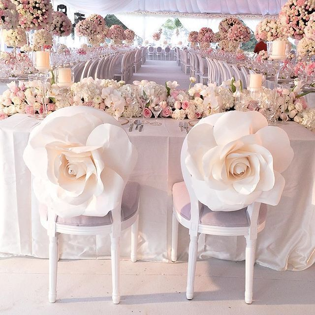 This wedding reception featured an abundance of beautiful blush-hued blooms, but we're especially taken with the massive paper roses fastened to the backs of the bride and groom chairs | WedLuxe Magazine